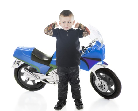 An adorable preschooler stretching his tatooed arms after a ride on his motorcycle.  On a white background.
