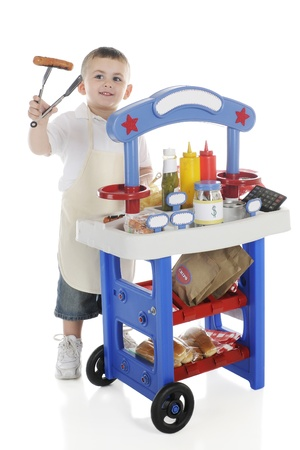 A young preschooler by his vendor stand holding a hot dog on the end of his tongs   The stand Stock Photo - 14089318