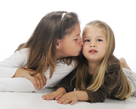 An elementary sister giving her little sister a kiss   On a white background