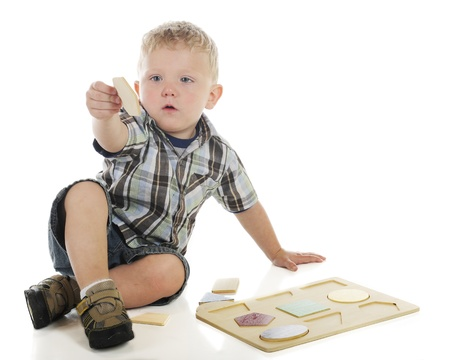 A young preschooler trying to figure out where the hexagon goes in his wooden shape puzzle   On a white background  Stock Photo - 14089424