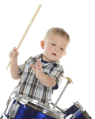 A young preschooler poised to strike the cymbol on his drum set   On a white background  Stok Fotoğraf
