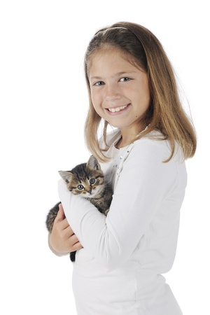 An attractive elementary girl proudly holding her pet kitten   On a white background  photo