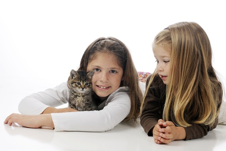 Sisters laying on the floor cuddling their kitty   On a white background  photo