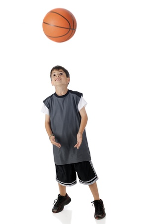 A young athelete looking up as he prepares to catch a basketball  Motion blur on basket ball   On a white background  photo