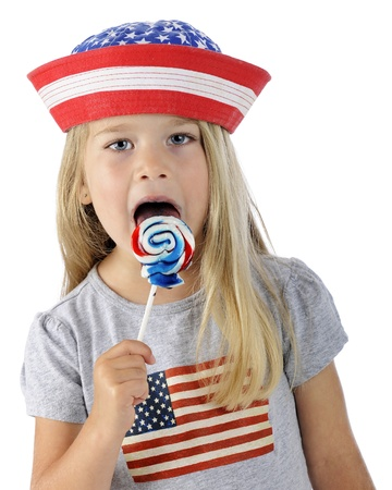 Closeup of an adorable preschooler wearing the stars and stipes while licking a swirly red, white and blue lollipop   On a white background  Stock Photo - 14089423