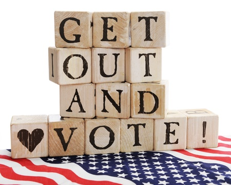 Rustic alphabet blocks arranged to say,  Get out and Vote   sitting on a bed of stars and stripes   On a white background  Imagens