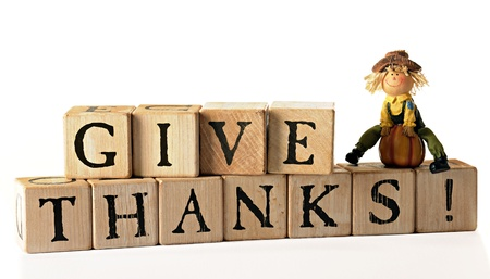 Rustic alphabet blocks arranged to spell out,  Give Thanks    A tiny scarecrow figurine with a pumpkin sits on top   Isolated on white   Imagens