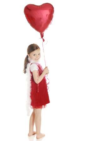 A barefoot elementary girl smiling back over her shoulder while holding a heart-shaped balloon.  Shes dressed in red with a fluffy white boa and strands of hearts.  On a white background.