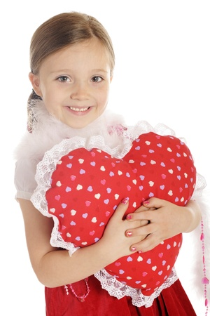 A beautiful elementary girl in red, hugging a heart shaped-pillow.  On a white background. Stock Photo - 14295582