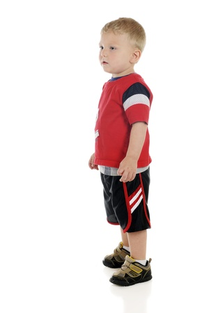 A near-profile full length image of a two year-old standing in his red and black sports shirt and shorts.  On a white background.