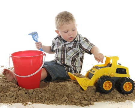 Playing with toys in wet sand, a young preschooler drops chucks of it onto his little bulldozer.  On a white background.