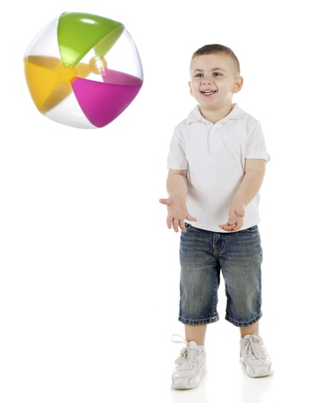 beachball: A young preschooler standing ready to catch a colorful beachball.  (Motion blur on beach ball.)  On a white background.