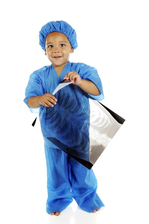 A biracial preschool doctor, in blue scrubs, happily holding a chest x-ray.  On a white background. Stock Photo - 14383505