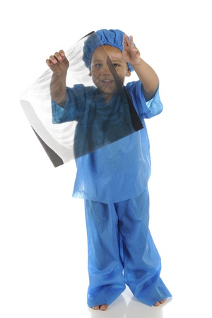 An adorable preschool doctor, wearing scrubs, happily holding a chest-x-ray and looking through it.  Focus on uncovered eye.  On a white background. Stock Photo - 14383471