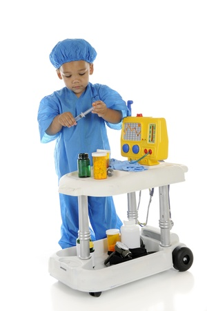 emergency cart: An adorable preschool doctor, in blue scrubs preparing medicine at his emergency cart.  On a white background.