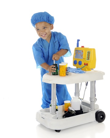 emergency cart: An adorable preschool doctor, happily drawing up medicine from his emergency cart.  On a white background.