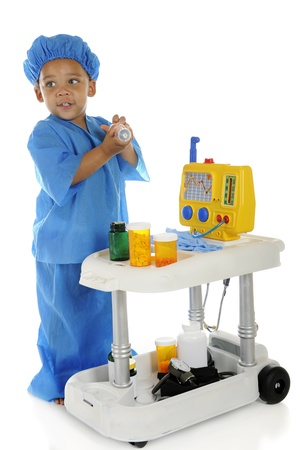An adorable preschool doctor, in blue scrubs filling a large syringe from medication on his emergency cart.  On a white background.
