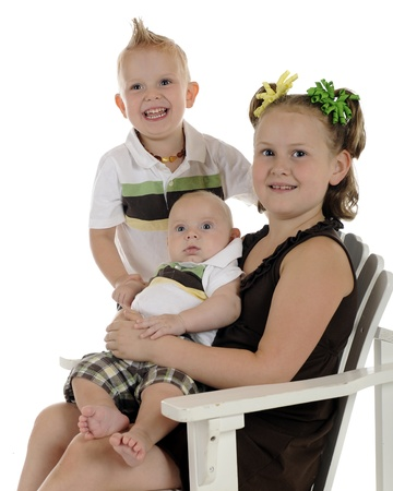 Portrait of three young siblings with focus on baby.  On a white background. Stock Photo - 14383393