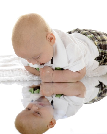 reflection in mirror: An infant looking at himself in a mirror below him.  On a white background.