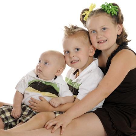 Retrato de una niña de primaria con su hermano pre-escolar y el bebé. Sobre un fondo blanco. Foto de archivo - 14383392