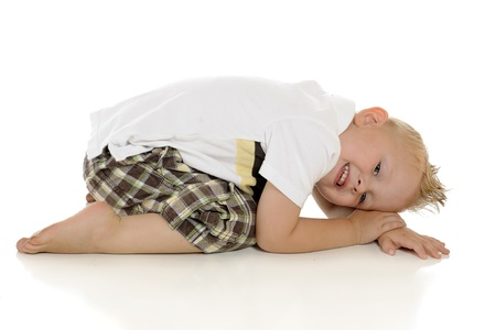 spiked hair: An adorable young preschooler on the floor scrunching up.  On a white background.