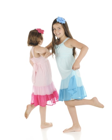 Two barefoot elementary girls frollicking with each other.  They're wearing identical outfits except one is pink, the other blue. Reklamní fotografie - 14383384