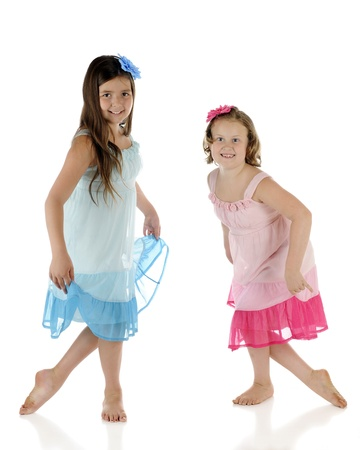 Two elementary girls happily dancing with each other.  Theyre wearing identical outfits except one is blue, the other pink.  On a white background. photo