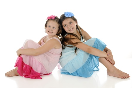 Two young girl friends, sitting back to back in look-alike sundresses, except one is pink and the other is blue.  On a white background. Stock Photo - 14383475
