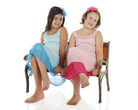 lookalike: Two happy elementary girl friends in look-alike sundresses (except one is blue, the other pink) sitting in similar fashion on a childs park bench.  On a white background.