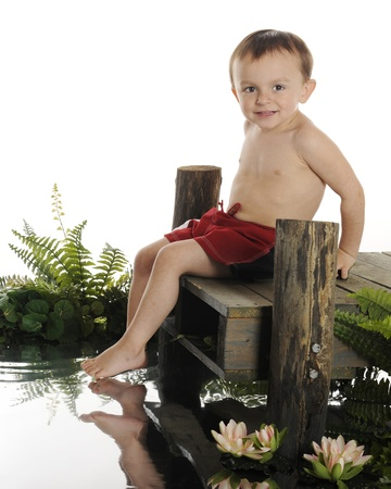 An adorable preschool swimmer ready to slide into the water from a rustic old dock   The dock is surrounded by water foliage   On a white background  photo