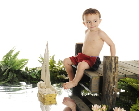 An adorable preschool  swimmer  sitting on a rustic, old dock sailing his toy sail boat  photo