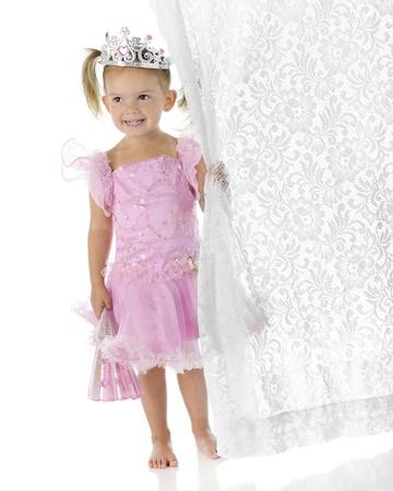 cortinas blancas: Un adorable princesa descalza preescolar con un abanico en una mano mientras que agarra una cortina de encaje blanco en los dem�s Sobre un fondo blanco
