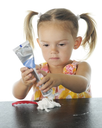 squeezing: An adorable preschooler concentrating on squeezing toothpaste onto her tooth brush   Focus on child