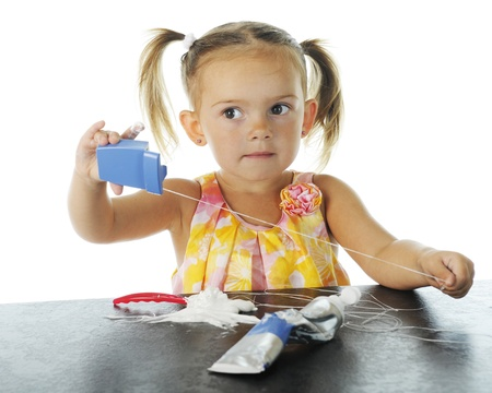 mess: An adorable preschooler who has made a mess loading her own toothbrush with tooth paste, and is pulling out all the floss   On a white background  Stock Photo