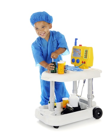 emergency cart: An adorable preschool doctor happily drawing up medicine from his emergency cart.  On a white background. Stock Photo