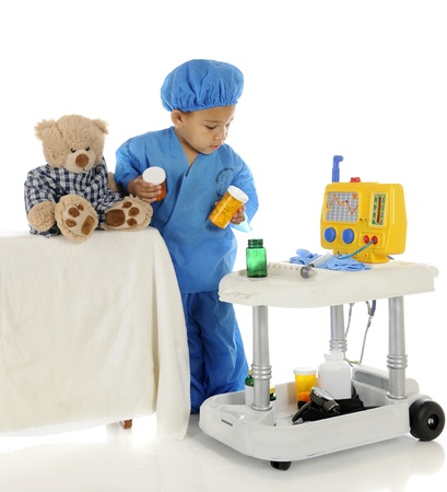 An adorable preschool doctor checking the meds on his emergency cart to give to his toy bear patient.  On a white background.  Imagens