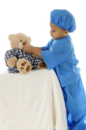 """An adorable preschool """"doctor"""" in blue scrubs, giving a pill to his toy bear whose wearing a hospital gown. On a white background."""