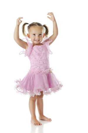 A barefoot preschooler wearing a pink ballerina dress with her arms arched over her head   On a white background