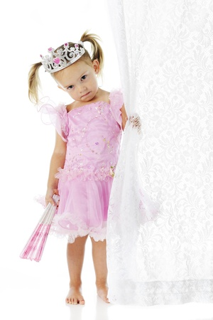 An adorable but sad preschool princess clutching a closed fan in one hand and a lacy curtain in the other.  On a white background. Stock Photo