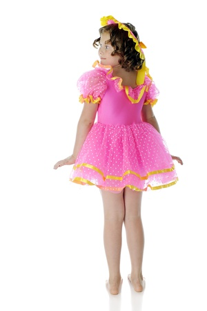 노란색 트림 주름 장식이 달린 분홍색 드레스와 모자를 입고 곱슬 머리를 가진 초등학교 아이의 후면보기. 흰색 배경에. 스톡 콘텐츠