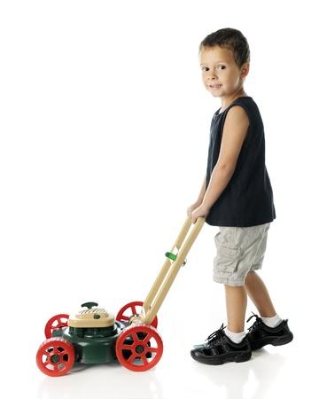 그의 장난감 잔디 깎는 기계 밀고 유치원 소년. 흰색 배경에. 스톡 콘텐츠