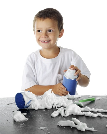 An adorable preschooler (missing a tooth) delightedly emptying a can of shaving cream on a black counter top.  On a white background. photo