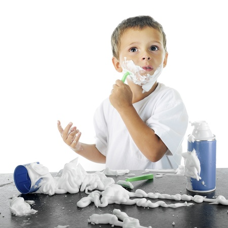 An adorable preschooler by a shaving cream mess looking up (into a mirror) as he attempts to shave like his dad.  On a white background. Stock Photo