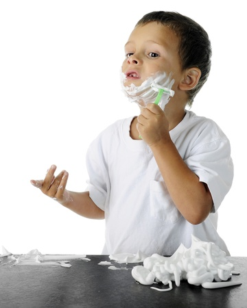 An adorable preschooler concentrating as he attempts to shave like his dad.  On a white background.