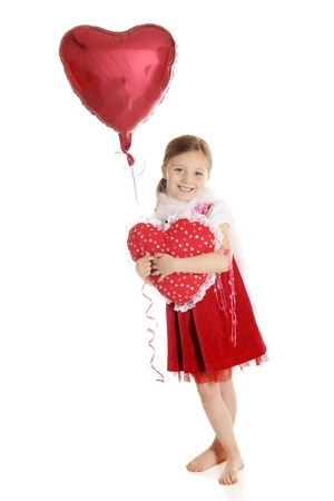 An adorable elementary girl hugging a heart-shaped pillow while holding the ribbon of a floating heart-shaped balloon   On a white background Stock Photo - 14668969