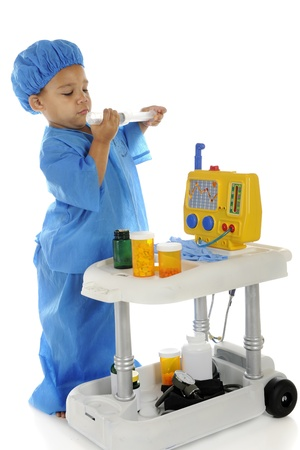 An adorable preschool  doctor  in blue scrubs checking the measurements on a large syringe as he stands by an emergency cart   On a white background  photo