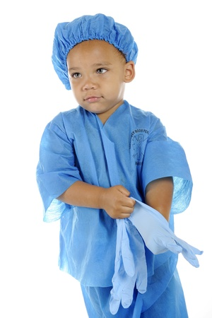 An adorable preschool  surgeon  in blue scrubs donning his surgical gloves   On a white background Stock Photo - 14668977