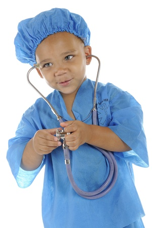 An adorable preschool  doctor  in blue scrubs preparing to listing to a patient
