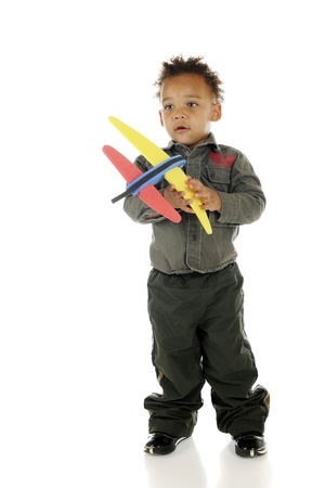 An adorable preschooler holding a toy airplane while wearing an air force outfit   On a white background Stock Photo - 14668968