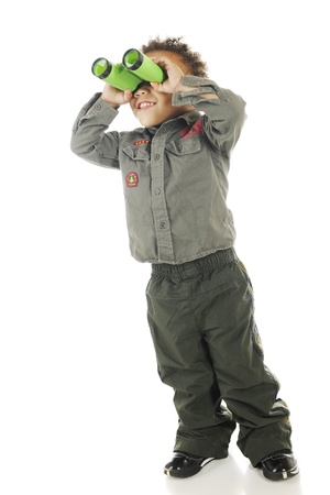 An adorable preschooler in Air Force garb happily looking up through binoculars   On a white background  Stock Photo - 14668976